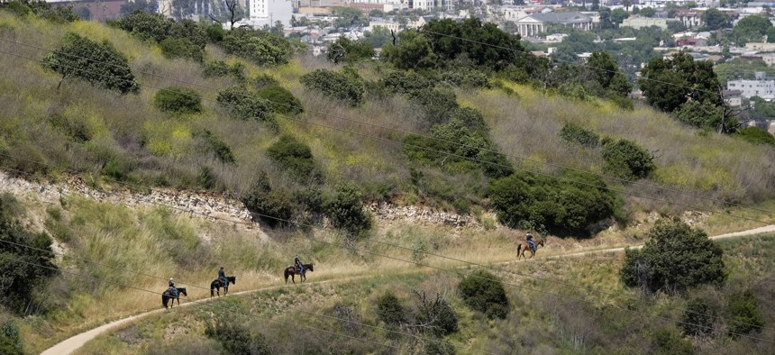 Riders on horseback advance down recently reopened hiking trails inside Griffith Park on May 14, 2020 in Los Angeles.