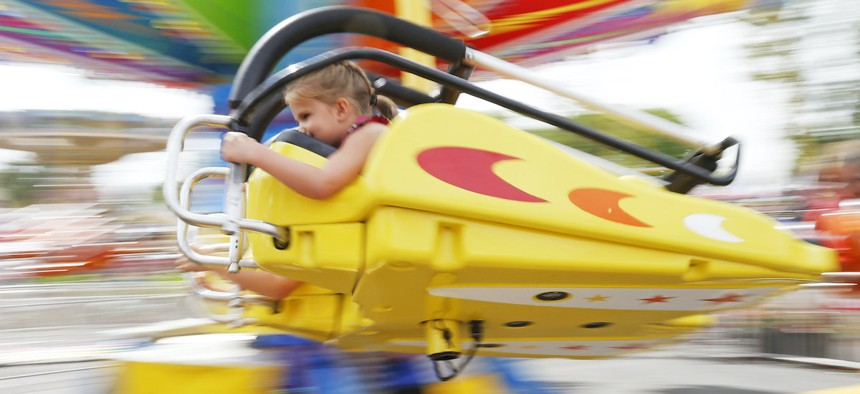 A young girl hangs on as she enjoys a ride at the Minnesota State Fair Tuesday, Aug. 30, 2016, in Falcon Heights, Minn.