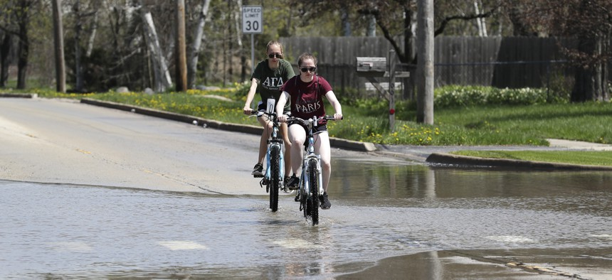 People ride bicycles on a flooded road in Waukegan, Illinois, north of Chicago.