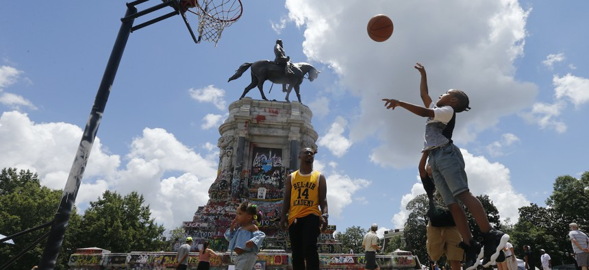 Isaiah Bowen, right, takes a shot as his dad, Garth Bowen, center, looks on at a basketball hoop in front of the statue of Confederate General Robert E. Lee on Monument Avenue Sunday June 21, 2020, in Richmond, Va.