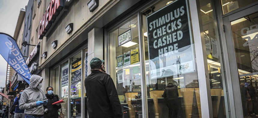 In this April 24, 2020, photo, people maintain social distancing and wear face masks due to COVID-19 concerns, while waiting to enter a check cashing service center in the Brooklyn borough of New York.