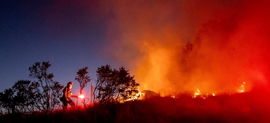A firefighter lights a backfire while working to contain the Crews Fire from near Gilroy, Calif., on July 5, 2020.