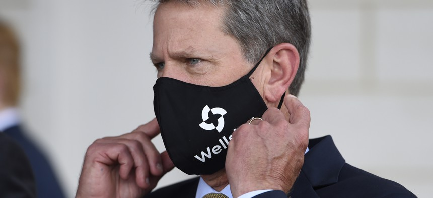 Georgia Gov. Brian Kemp adjusts his mask prior to a bill signing at Wellstar Kennestone Hospital where the hospital opened a new Emergency Room space, Thursday, July 16, 2020, in Marietta, Ga.