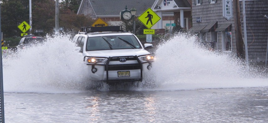 A car drives through a flooded road in Bay Head, N.J. on Friday Oct. 11, 2019, after a combination of high tides and strong winds caused minor to moderate flooding along parts of the shore.