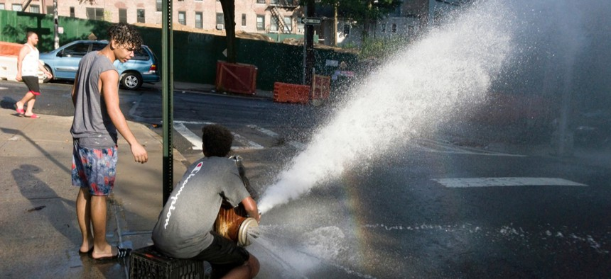 Children in the Bronx, New York, use a fire hydrant to cool off.