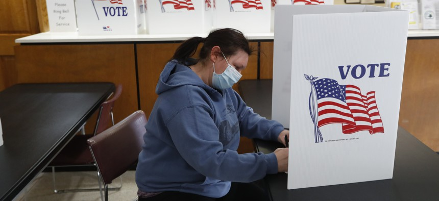 In this Tuesday, May 5, 2020 file photo, a voter fills out an absentee ballot at City Hall in Garden City, Mich., as about 50 Michigan communities participate in largely mail-based local elections.