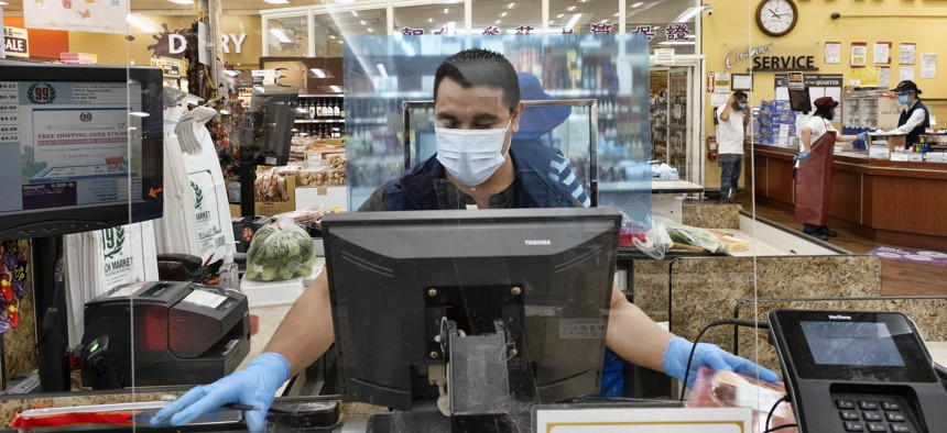 A grocery store worker checks out customers in Los Angeles.