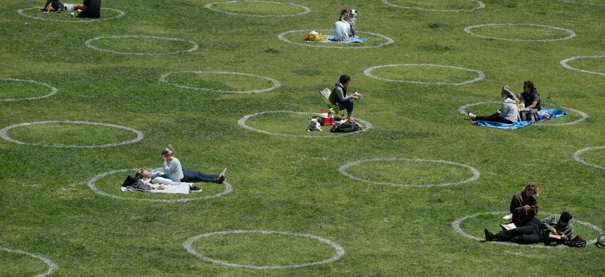 Visitors set up inside circles designed to help prevent the spread of the coronavirus by encouraging social distancing, at Dolores Park in San Francisco on June 28, 2020.