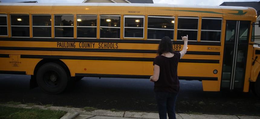 A mom waves goodbye to a school bus on Aug. 3 in Dallas, Ga.