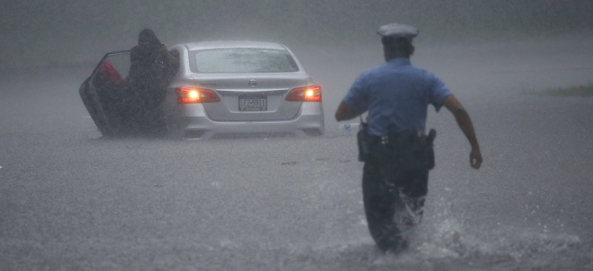 A police officer rushes to help a stranded motorist during Tropical Storm Isaias, Tuesday, Aug. 4, 2020, in Philadelphia. The storm spawned tornadoes and dumped rain during an inland march up the East Coast after making landfall as a hurricane.