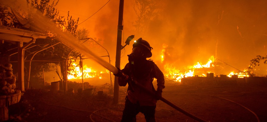 A firefighter works against the Lake Hughes fire in Angeles National Forest on August 12, 2020.