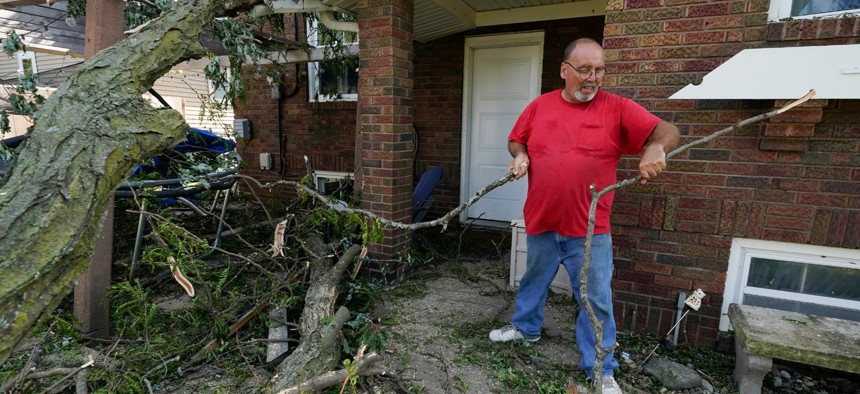 Cecil Gott removes a fallen tree that rests on the back of a neighbor's home, Friday, Aug. 14, 2020, in Cedar Rapids, Iowa.