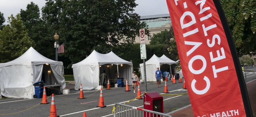 Members with the Washington, D.C. Dept. of Health administer Covid-19 tests on F Street on Aug. 14, 2020. This location tests approximately 450-500 people per week and has been open since June 1. (AP Photo/Alex Brandon)