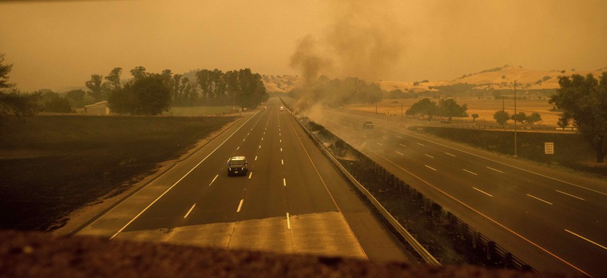 A police vehicle drives along Interstate 80, which was closed when flames from the LNU Lightning Complex fires jumped the roadway, in Vacaville, Calif., on Wednesday, Aug. 19, 2020.