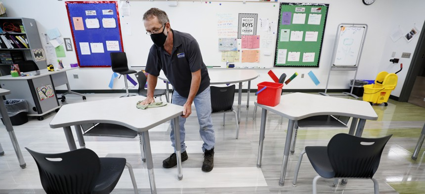 In this July 29, 2020 file photo, custodian Doug Blackmer wipes down a desk in a classroom at the Jesse Franklin Taylor Education Center in Des Moines, Iowa.