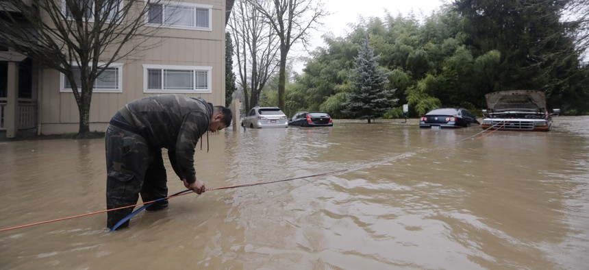 Ricardo Guerrero tries to rig a tow line to his flooded truck and return it to high ground at his flooded apartment complex on Feb. 6, 2020, in Issaquah, Wash.