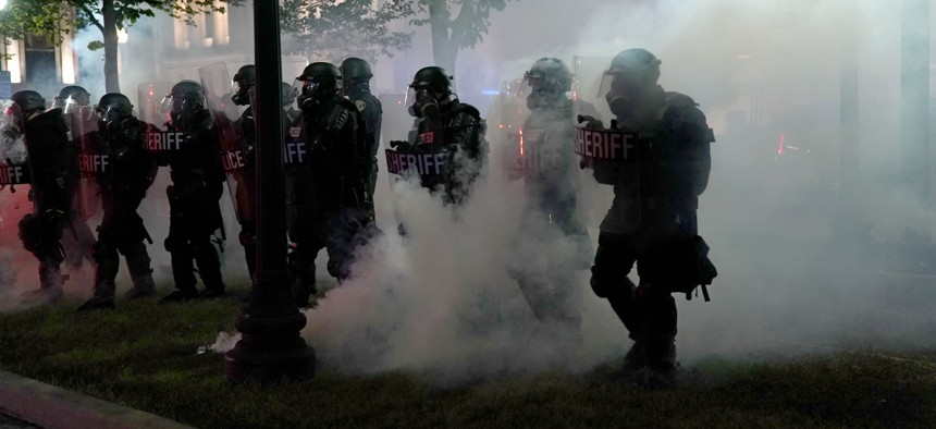 Police clear a park during clashes with protesters outside the Kenosha County Courthouse late Tuesday, Aug. 25, 2020, in Kenosha, Wis., during demonstrations over the Sunday shooting of Jacob Blake.