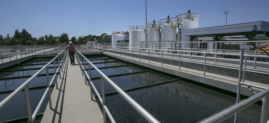 A supervisor tours the Secondary Treatment Clarifiers tanks at the Los Angeles Sanitation plant where millions of gallons of wastewater are purified each day in Van Nuys, Calif., Wednesday, May 20, 2015.