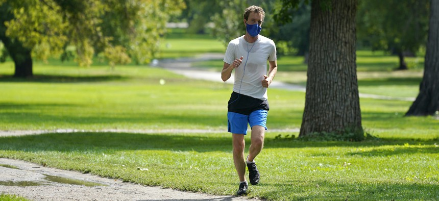 A lone runner wears a face covering while moving along a path in City Park early Friday, Aug. 28, 2020, in east Denver. (AP Photo/David Zalubowski)