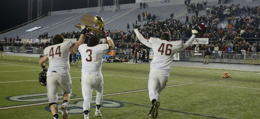 St. Joseph Prep's players run with the championship trophy to fans after a championship football game against Pine-Richland in Hershey, Pa. on Saturday, Dec. 13, 2014. St Joseph won 49-41. (AP Photo/Ralph Wilson)