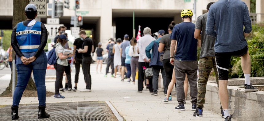 People wear masks as they wait in line to vote at a voting center during primary voting in Washington, Tuesday, June 2, 2020.