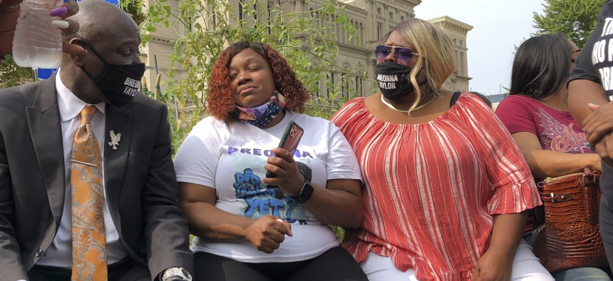 Tamika Palmer, Breonna Taylor's mother, in white beside Attorney Ben Crump, left, speak in Louisville, Ky., after settlement was announced.