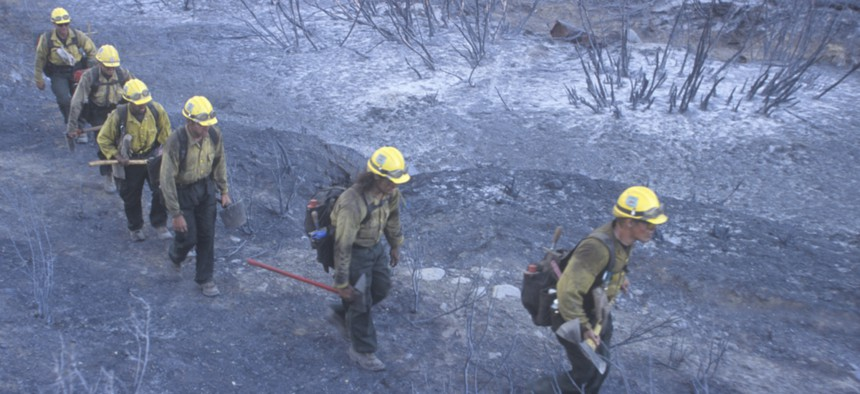 Firefighters in California walk through an area ravaged by wildfires.