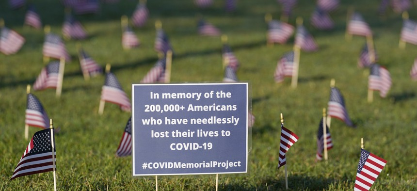 Activists from the COVID Memorial Project mark the deaths of 200,000 lives lost in the U.S. to COVID-19 after placing thousands of small American flags places on the grounds of the National Mall in Washington, Tuesday, Sept. 22, 2020.