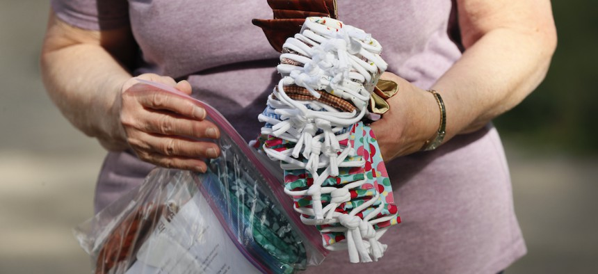 A Des Moines Area Quilters Guild member drops off completed face masks to be distributed to Des Moines Public Schools students, Thursday, July 30, 2020, in Des Moines, Iowa. (AP Photo/Charlie Neibergall)