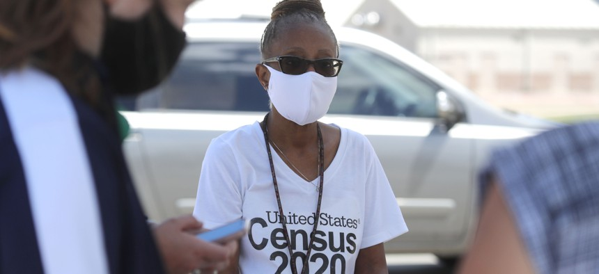 Amid concerns of the spread of COVID-19, census worker Jennifer Pope wears a mask and sits by ready to help at a U.S. Census walk-up counting site set up for Hunt County in Greenville, Texas on July 31, 2020.
