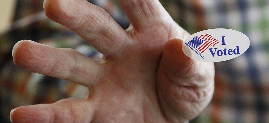 """Ridgeland, Miss., precinct worker Cliff Smith offers people a """"I Voted"""" sticker as they exit after voting in the party presidential primary, Tuesday, March 10, 2020. (AP Photo/Rogelio V. Solis)"""