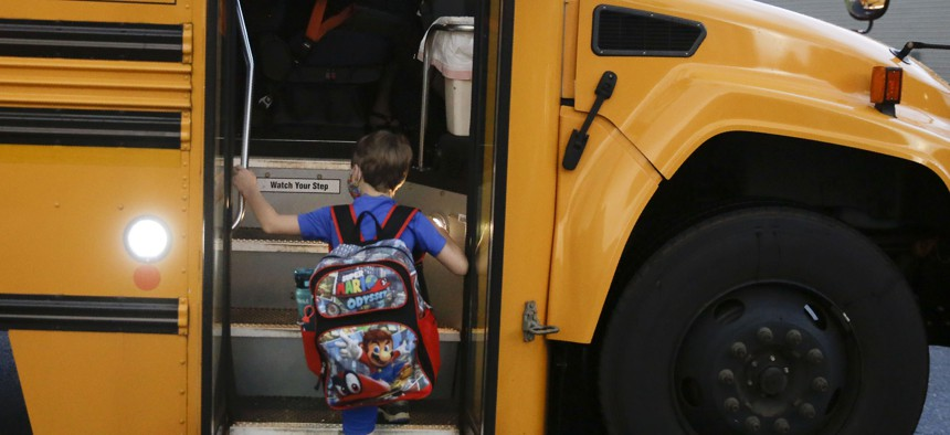 Paul Adamus, 7, climbs the stairs of a bus before the fist day of school on Aug. 3, 2020, in Dallas, Ga.