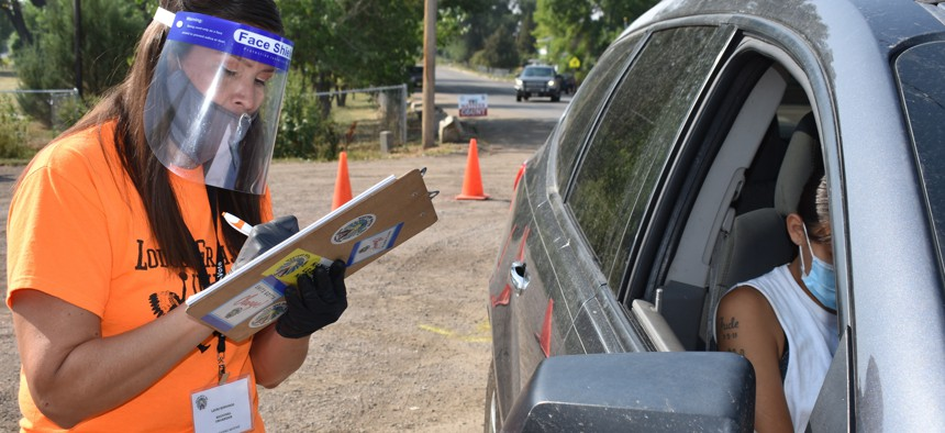 In this Aug. 26, 2020 photo, Lauri Dawn Kindness, left, helps a family participate in the U.S. Census as part of a campaign to increase Native American participation in the count, on the Crow Indian Reservation, in Lodge Grass, Montana.
