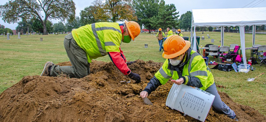 Workers sift through dirt excavated in the Oaklawn Cemetery in Tulsa, Oklahoma.