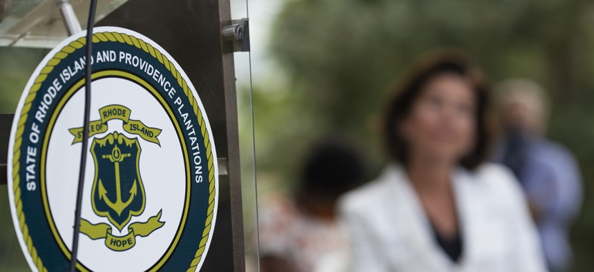 """The Rhode Island seal decorates a podium as Democratic Gov. Gina Raimondo looks on during a June news conference announcing the removal of the phrase """"Providence Plantations"""" from the state's formal name in official documents and websites."""