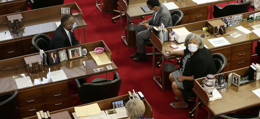 A limited number of lawmakers gather on the House floor as the North Carolina General Assembly opens a new session amid the current COVID-19 stay-at-home restrictions in Raleigh, N.C., Tuesday, April 28, 2020. (AP Photo/Gerry Broome)