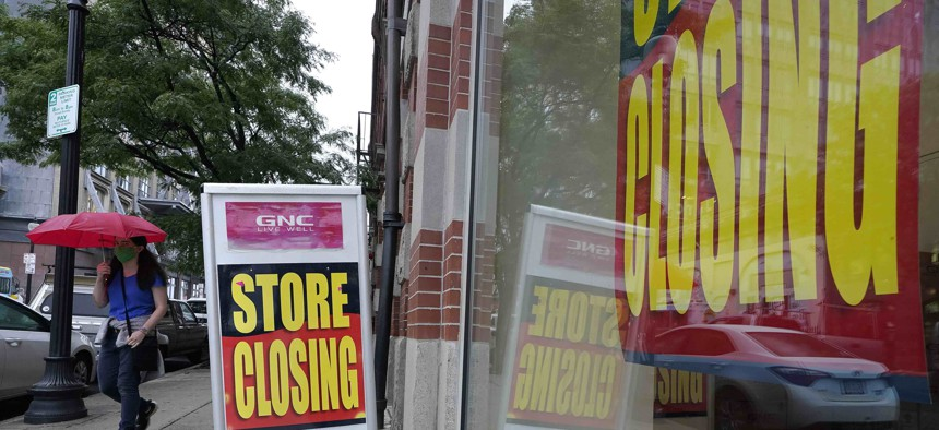 In this Sept. 2, 2020 photo a passerby walks past a business storefront with store closing signs in Boston.
