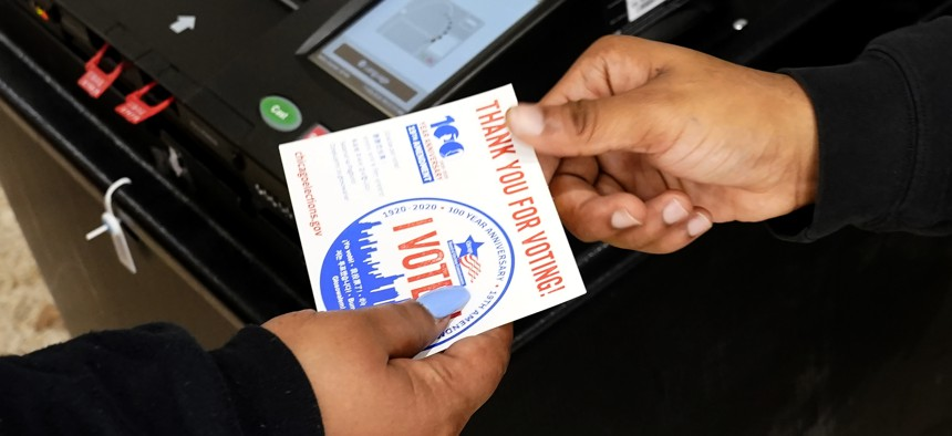 """A poll worker hands a voter their """"I Voted"""" sticker on Election Day."""