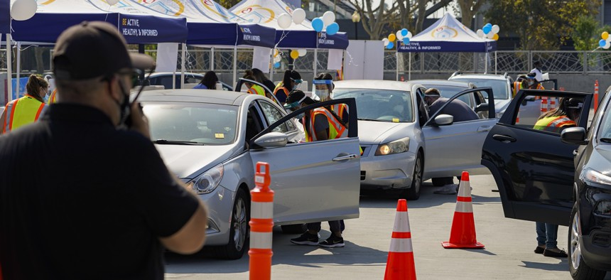 People wait inside their vehicles to get their influenza vaccine during a free drive-thru flu vaccination event at the Exposition Park in Los Angeles, Saturday, Oct. 17, 2020.