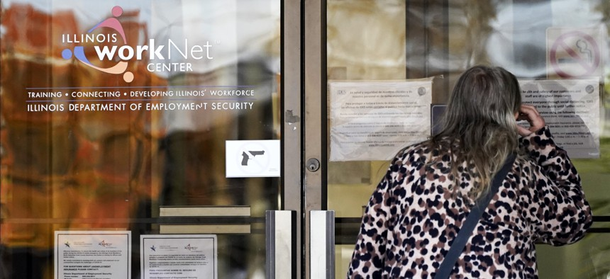 A woman checks information as information signs are displayed at IDES (Illinois Department of Employment Security) WorkNet center in Arlington Heights, Ill., Thursday, Nov. 5, 2020.
