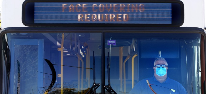 Metro Breez bus driver Rich Price, wearing a face mask, waits at a bus stop on May 13, 2020, in Portland, Maine.
