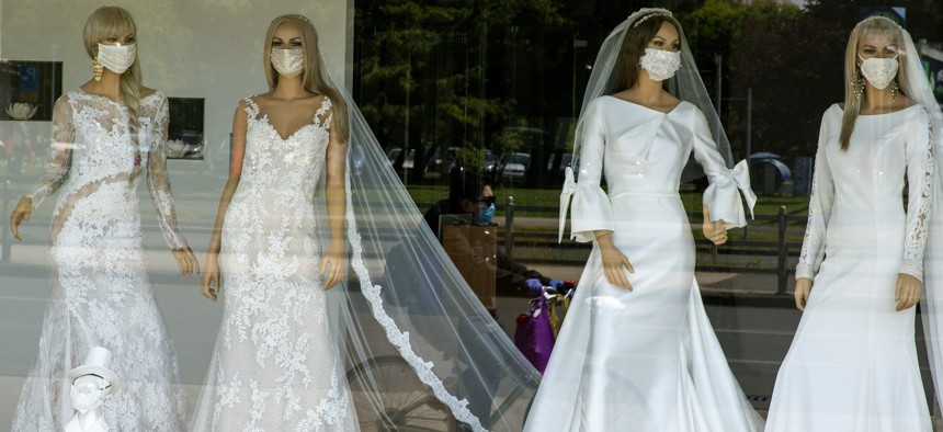 A cyclist wearing a protective mask to protect against coronavirus is reflected in the window of a wedding dress store with mannequins wearing face masks on Thursday, April 23, 2020.