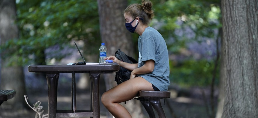 In this Aug. 18, 2020, file photo, a student works outside Ehrighaus dormitory on campus at the University of North Carolina in Chapel Hill, N.C.