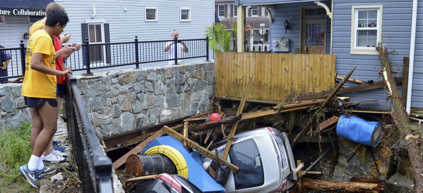Residents on May 28, 2018 gather by a bridge to look at cars left crumpled in one of the tributaries of the Patapsco River that burst its banks as floodwaters channeled through historic Main Street in Ellicott City, Md.