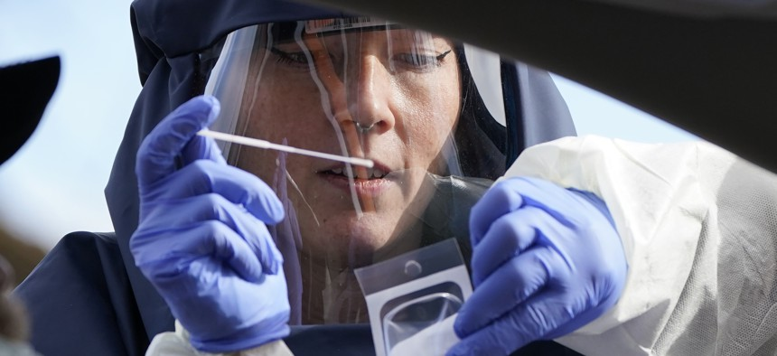 A Salt Lake County Health Department public health nurse performs a coronavirus test at the Salt Lake County Health Department Friday, Nov. 13, 2020, in Salt Lake City.