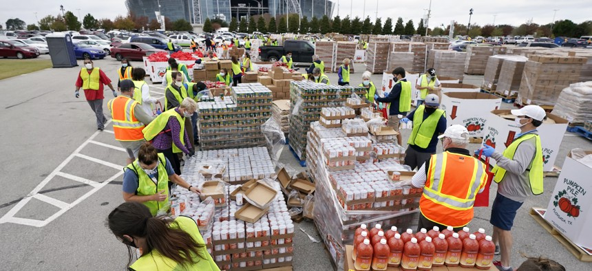 Volunteers build bags of dry goods in a parking lot outside of AT&T Stadium during a Tarrant Area Food Bank mobile pantry distribution event in Arlington, Texas, Friday, Nov. 20, 2020.