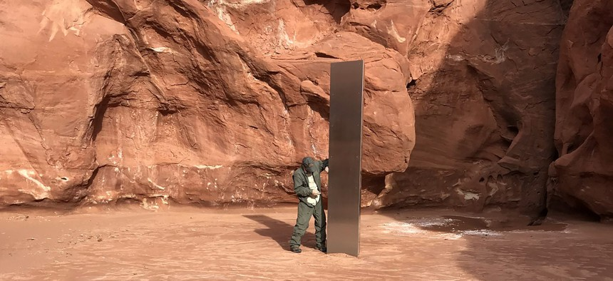 In this Nov. 18, 2020, file photo provided by the Utah Department of Public Safety, a Utah state worker stands next to a metal monolith in the ground in a remote area of red rock in Utah.