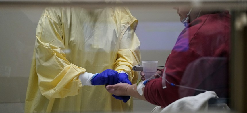 A registered nurse hands medication to a Covid-19 patient inside the emergency room at Scotland County Hospital in Memphis, Mo., on Nov. 24, 2020.