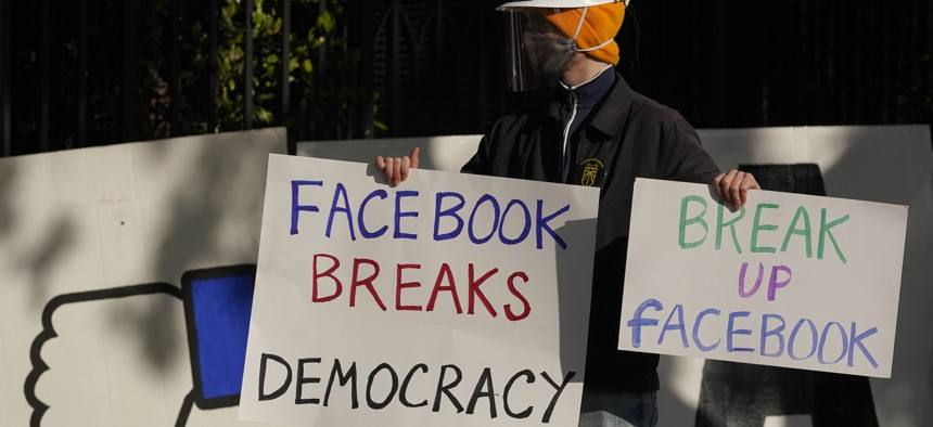 In this Saturday, Nov. 21, 2020, file photo, a demonstrator joins others outside of the home of Facebook CEO Mark Zuckerberg to protest what they say is Facebook spreading disinformation in San Francisco.