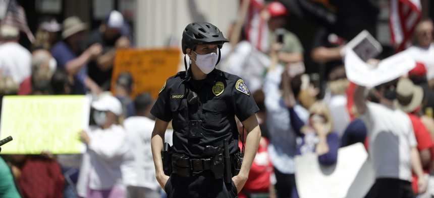 A San Diego police officer looks on during a protest against measures aimed at slowing the spread of the new coronavirus on May 1, 2020, in San Diego, California.